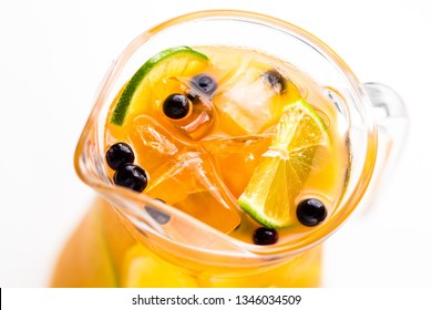 Refreshing non-alcoholic summer drink with orange in a glass pitcher close up, soft focus