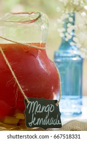 A refreshing pitcher of mango lemonade at an outdoor party.