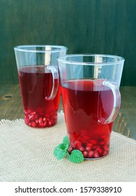 Refreshing pomegranate tea, red drink with mint in two tall glass mugs on burlap, over dark green background