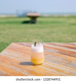 Refreshing with Sakura Yuzu Lemonade on wood table and green background by the sea.