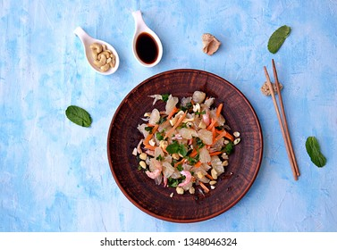 Refreshing salad with pomelo, shrimps, carrots and cashew nuts on a light blue background. Asian cuisine. Top view.