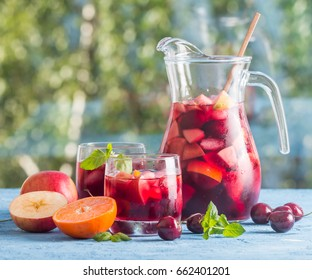 Refreshing sangria or punch with fruits in glasses and pincher