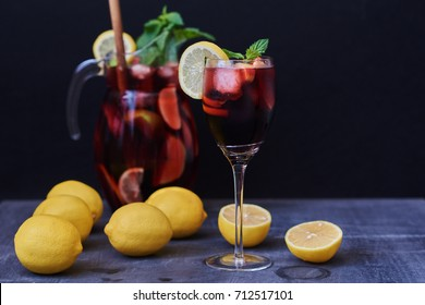 Refreshing sangria or punch with fruits in glasses and pitcher. Traditional summer drink sangria. Red wine, strawberries, oranges, lemon, green apple and grapefruit. On a black table. Copy space.