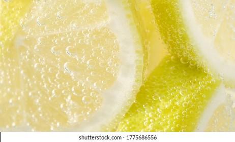 refreshing soda tonic fizzy water, lemon in glass macro close-up. Slice of lemon, mineral bubbles. lemonade