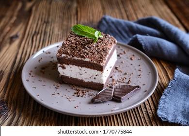 Rafraîchissement du gâteau Stracciatella saupoudré de copeaux de chocolat servi sur une plaque de céramique