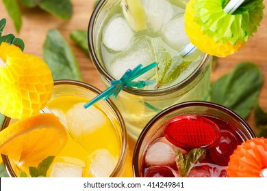 Refreshing summer cocktails, with orange, kiwi and cherry. Mint leaves on wooden background