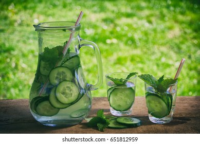 Refreshing summer cucumber drink in the garden. Fresh sliced cucumber with mint leaves in a glass of water. Detox drink with antioxidant.