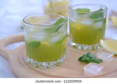 Refreshing summer drink, lemonade with cucumber juice and basil. Served in glass glasses with ice and straw
