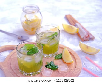 Refreshing summer drink, lemonade with cucumber juice and basil. Served in glass glasses with ice and straw. Healhty drink concept.