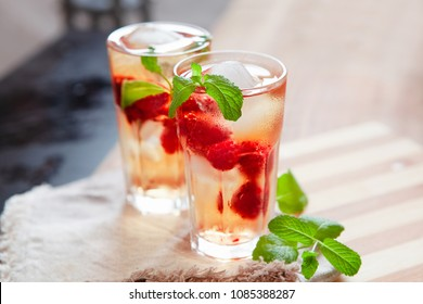 Refreshing summer drink with syrup, raspberry, mint and ice. Glasses with cold and healthy beverage, place for text