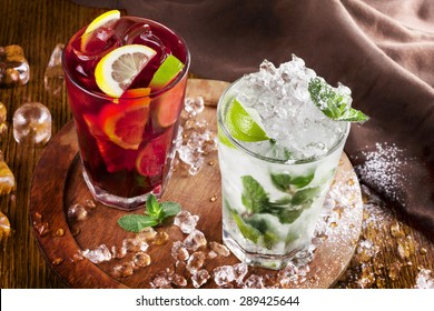 a refreshing summer drinks on a rural texture. authentic picture . mojito and sangria. focus on the surface of beverage