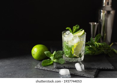 Refreshing summer mojito cocktail with ice cubes, fresh mint and lime on black. Exotic mojito beverage.