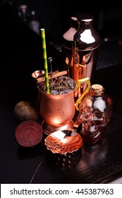 Refreshing summer punch and copper bar tools on dark background