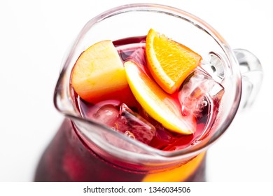 Refreshing summer red wine sangria drink in a glass pitcher close up, soft focus