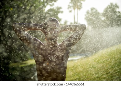 Refreshing summer silhouette of man standing under shower of water drops in a tropical green landscape