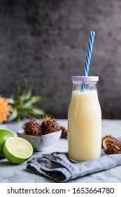Rafraîchir l'ananas et le smoothie rambutan avec du lait de coco dans une bouteille de verre