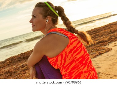 Refreshing wild sea side workout. Seen from behind relaxed young healthy woman in sport clothes on the beach looking into the distance and listening to the music with headphones