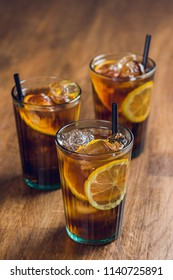 Refreshingly cold ice tea with lemon on wooden table
