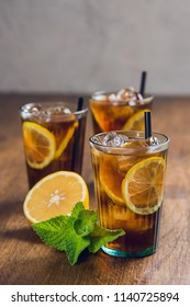 Refreshingly cold ice tea with lemon and mint on wooden table
