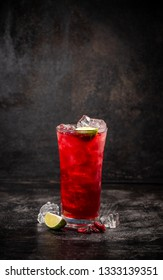Refreshment alcoholic red cranberry and lime cocktail with ice on dark background, copy space