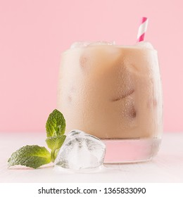 Refreshment baileys creamy cocktail in misted glass with ice cubes, green mint, straw in pink interior on white wooden table, closeup, details, square.