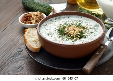 Refreshment bulgarian dish tarator in brown bowl on wooden table. Summer cold soup with yogurt and cucumber for healthy diet. Copy space.