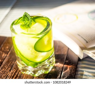 Refreshment drink with cucumber and mint leaves next to study book