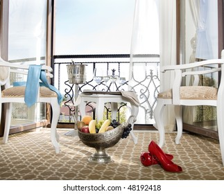 refreshment in front a balcony . Still life photo of a hotel room with service of drink and fruit in front to a balcony.