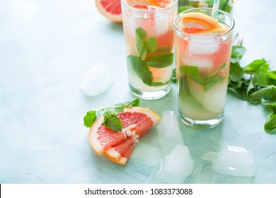 Refreshment grapefruit cocktail with mint on mint color background. Healthy citrus summer drink.