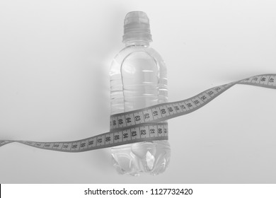 Refreshment and healthy regime symbols. Bottle made of plastic wrapped with turquoise ruler. Athletics and weight loss concept. Water bottle tied with cyan measure tape on light grey background.