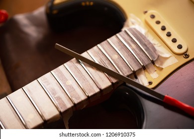 Refretting an electric. Electric guitar in  a guitar repair shop with file on fret. Double cutaway solid body guitar.