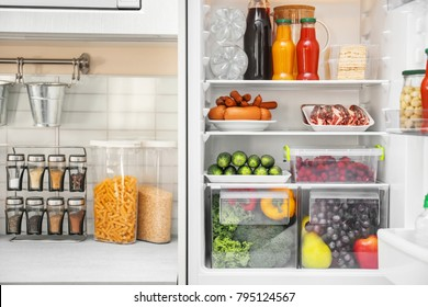 Refrigerator with different products in kitchen