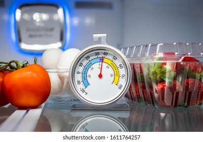 Refrigerator thermometer with colorful food in cold storage unit. Refrigeration safety gauge displaying safe food temperature.