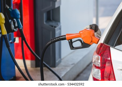 Refuel automobile ; filling petrol or gas tank at filling station.