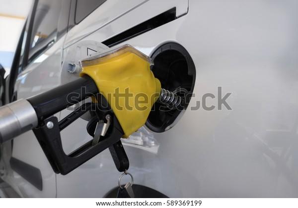 Refueling car at a gas station. Car fuel tank and petrol pump