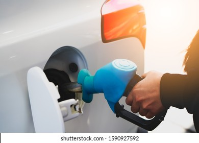Refueling car in gasoline station. Woman driver hand squeeze the handle, fill the tank with petrol, self-service.