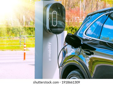 Refueling for cars e-mobility. Charging an electric car at hybrid engine gasoline and electricity. Sunlight as an electric renewable energy concept
