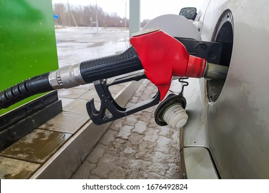 Refueling gun in the gas tank of a silver car. Refueling nozzle in a car tank at a gas station.