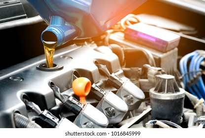 Refueling and pouring oil into the engine motor car on isolated white background. Energy fuel and saving energy concept.