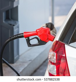Refuelling automobile ; filling petrol or gas tank at filling station.