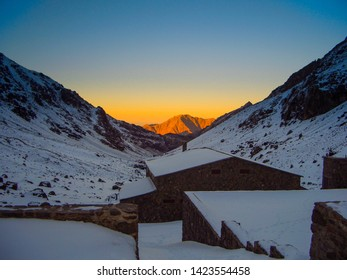 Refuge de Toubkal, below Jebel Toubkal in the Atlas mountains of Morocco with a yellow sunset caused by the sand of the desert.