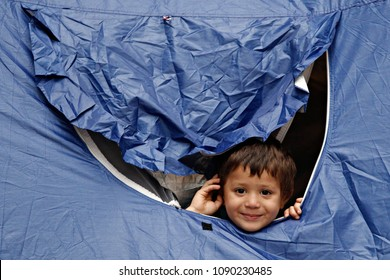 A Refugee boy sits in tent in Victoria Square, where migrants and refugees stay temporarily in Athens, Greece on Sep. 22, 2015.
