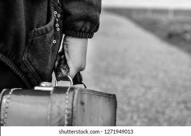 Refugee girl walking on the road on the countryside with her old suitcase