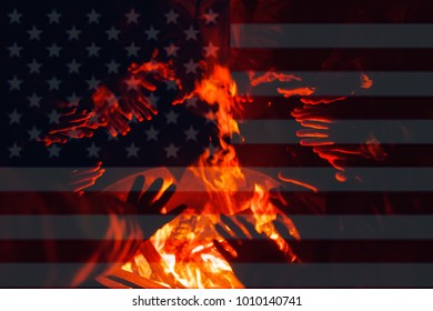 Refugees, illegal immigrants in America are warming their hands in fire of barrel. American flag