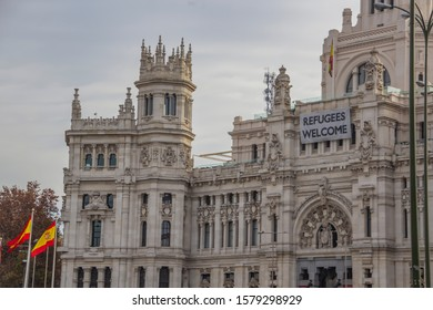 "Refugees Welcome"" message on Palacio de Cibeles in Madrid with spain flags"