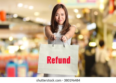 """"""" REFUND """" text on bag hold by smiling woman with blur shopping mall background"""