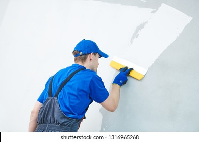 refurbishment. Plasterer worker spackling a wall with putty