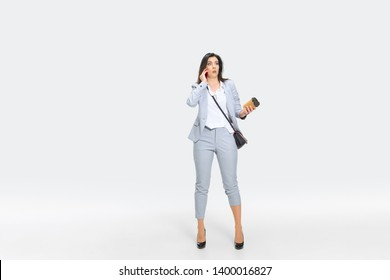 I refuse to understand. Young woman in gray suit is getting shocking news from boss or colleagues. Looking numbed while dropping coffee. Concept of office worker's troubles, business, stress.