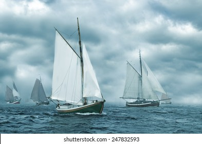 Regatta of old sailing boats coming out of the fog.