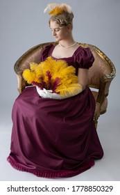 A Regency woman in a maroon evening dress on a plain studio backdrop